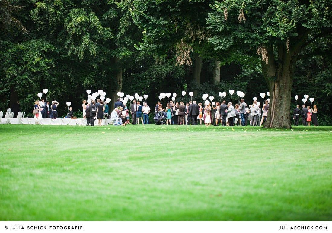 Hochzeitsgesellschaft auf Burg Hülshoff mit Luftballons nach freier Trauung