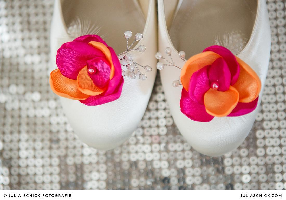 Detail Brautschuhe mit pink-orangenen Blüten auf Paillettenkissen