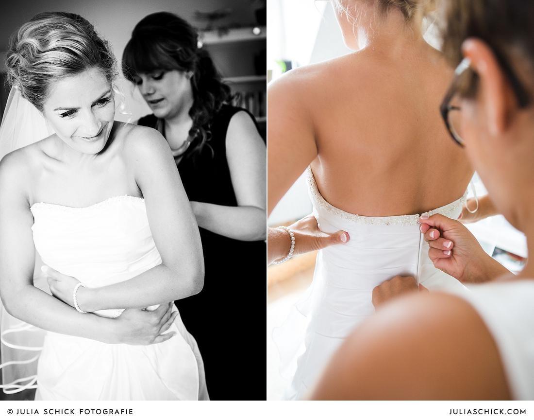 Trauzeugin hilft Braut ins Kleid