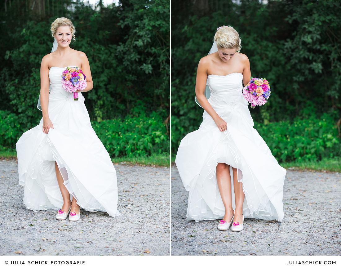 Braut zeigt Brautschuhe mit Ansteckern