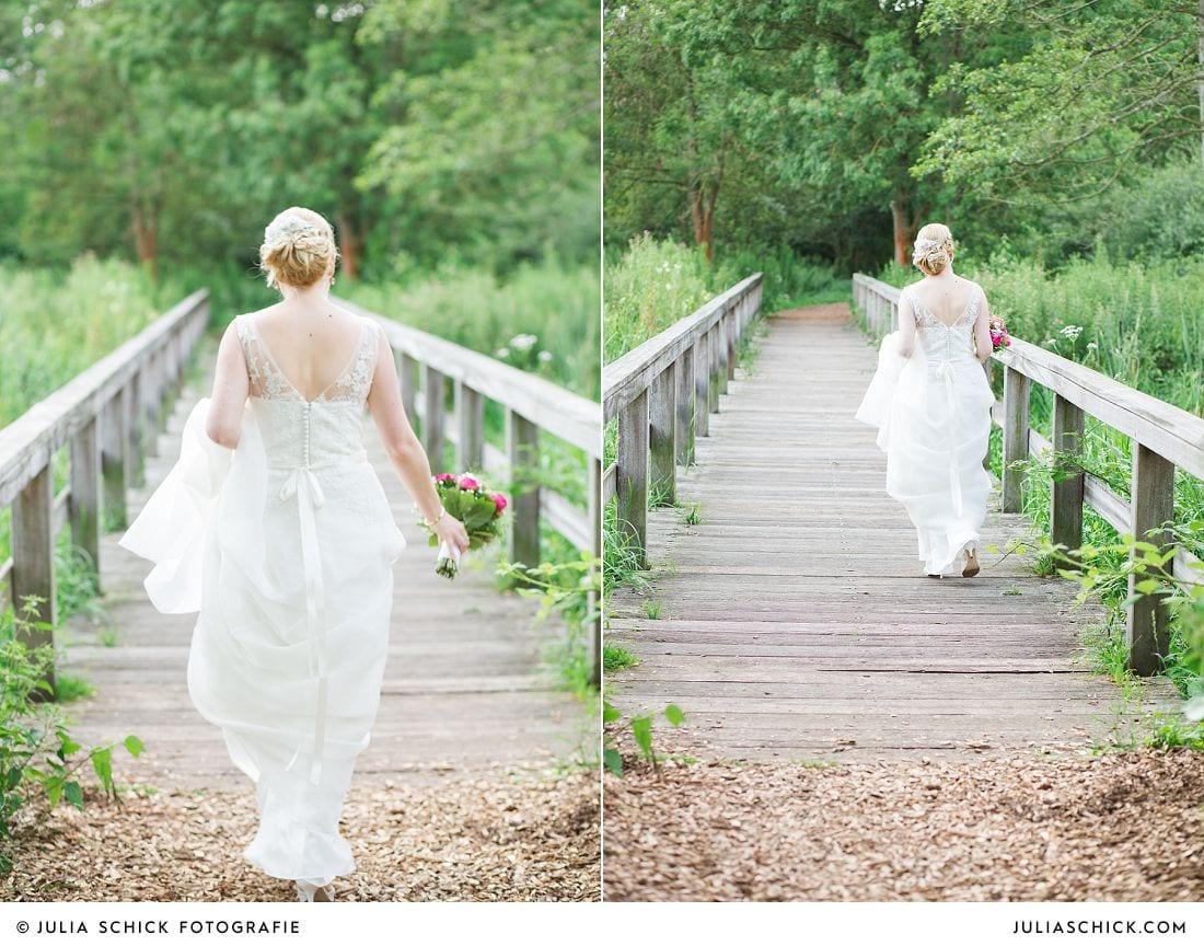 Braut läuft Brücke im Wienburgpark entlang