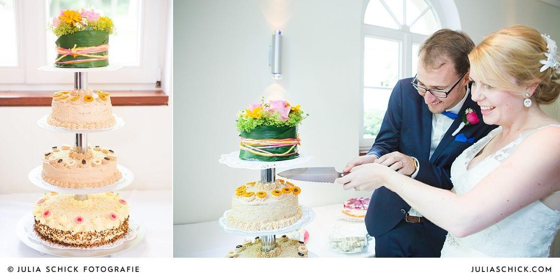 Hochzeitspaar schneidet Hochzeitstorte auf gut Havichhorst in Münster an