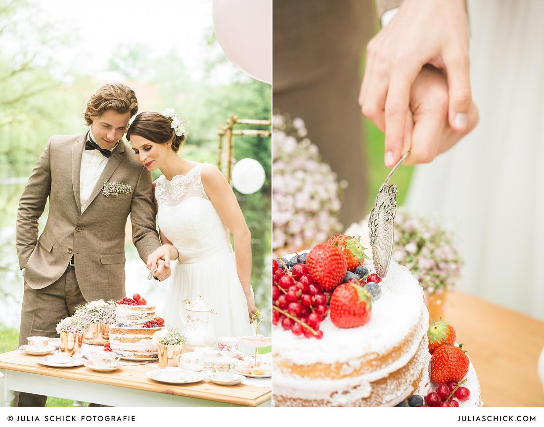 Brautpaar schneidet Naked Cake mit Früchten im Vintage Stil am Hof zur Linde
