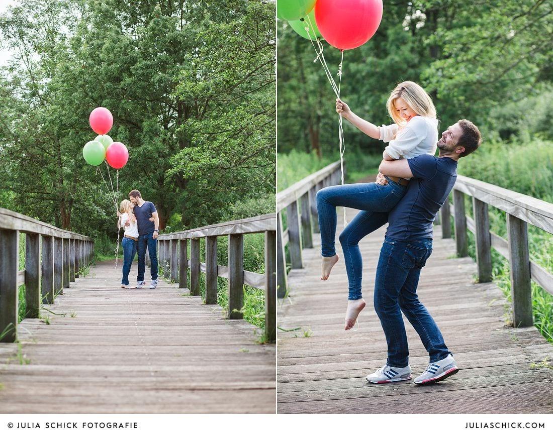 Verlobtes Paar mit roten und grünen Ballons im Wienburgpark