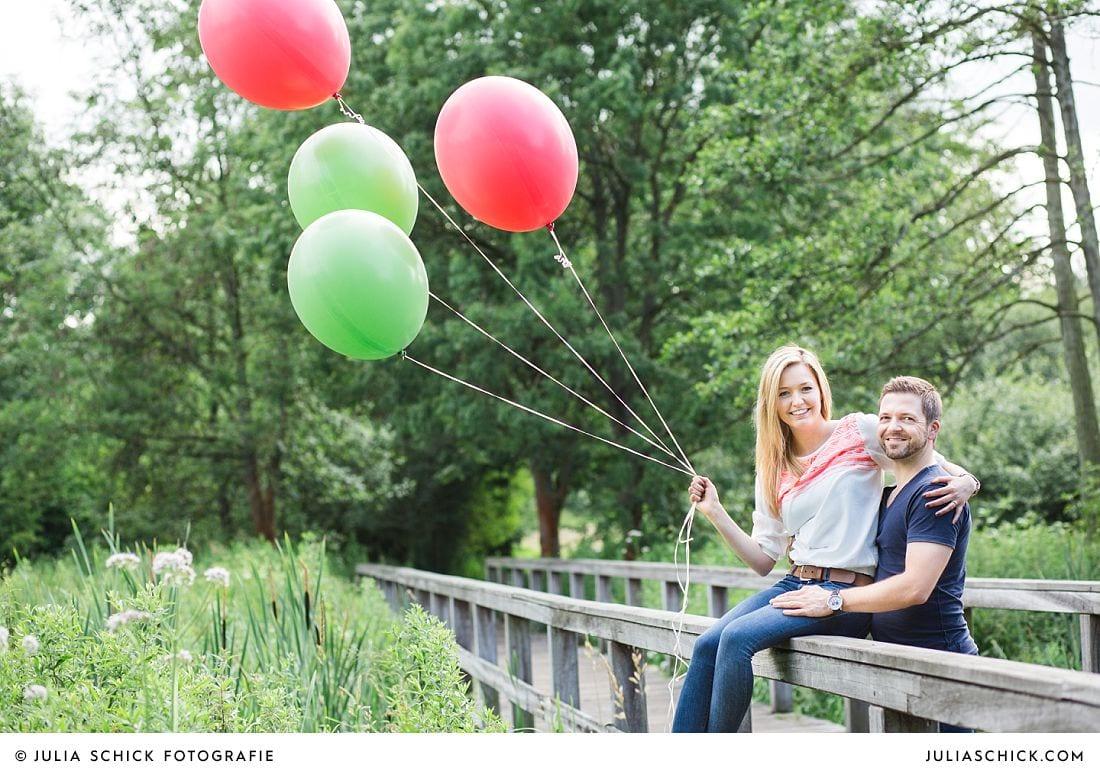 Engagementshooting mit roten und grünen Ballons im Wienburgpark