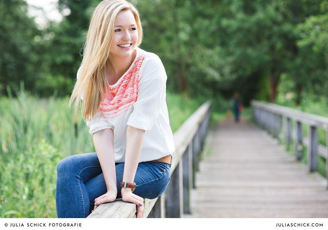 Hübsche blonde Frau auf Brücke im Wienburgpark Münster