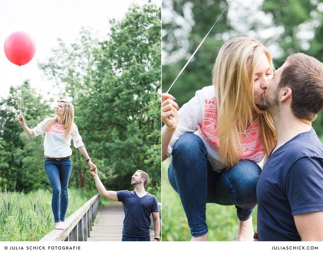 Frau balanciert auf Balustrade einer Brücke mit roten und grünen Ballons im Wienburgpark