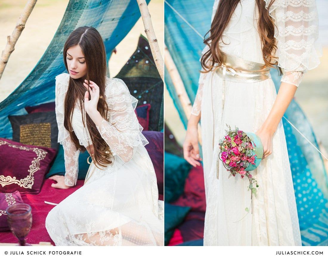 Boho Hochzeit Braut im Boho Spitzenkleid vor Boho Zelt mit vielen Kissen