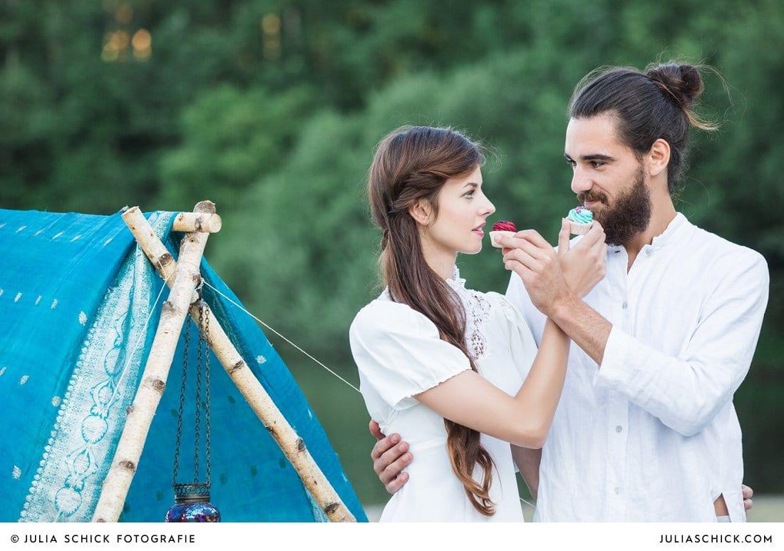 Boho Brautpaar beißt in Cupcakes