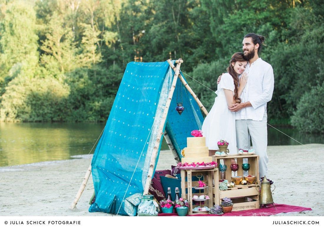 Hochzeitsfoto lächelndes Brautpaar Hippie-Zelt aus Sari mit Hochzeitstorte und Candybar