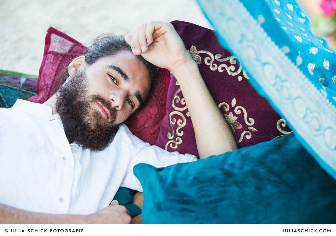 Bärtiger Mann auf bunten Kissen, Boho Hochzeitsshooting