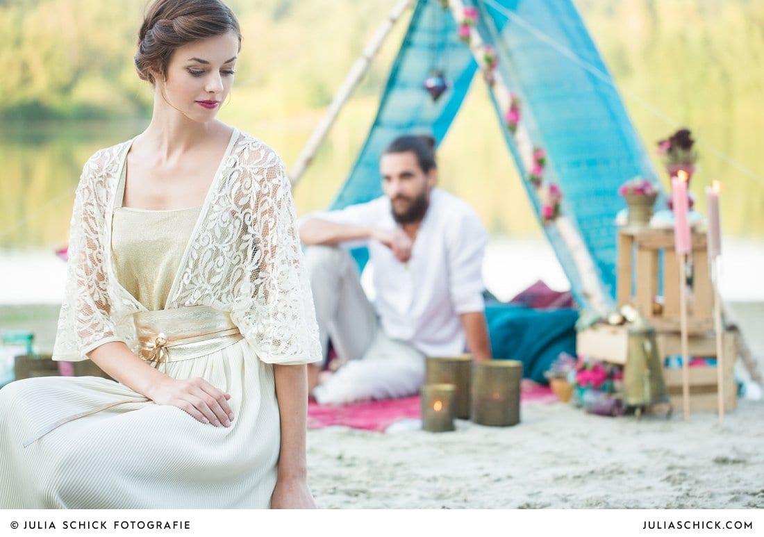 Braut im goldenen Spitzenbrautkleid sitzend vor Boho-Zelt mit Bräutigam im Zelt