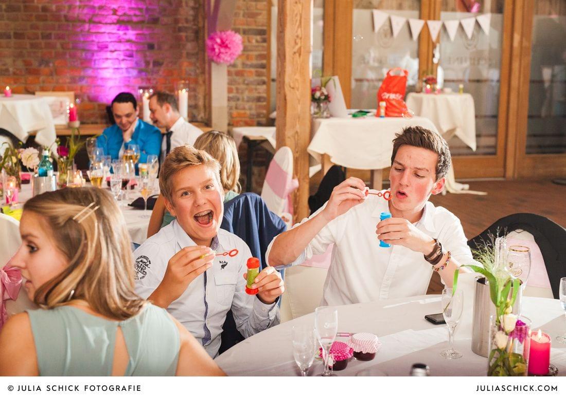 Gäste mit Seifenblasen bei einer Hochzeit auf Gut Kump
