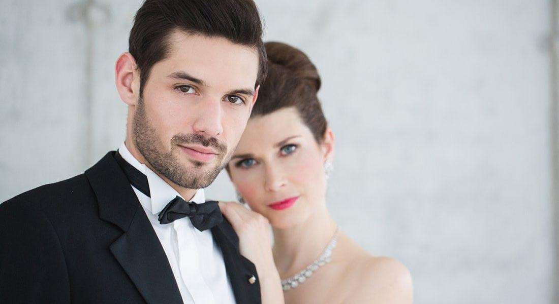 Hochzeitspaar in Smoking und silbernem Brautkleid vor Sichtbetonwand