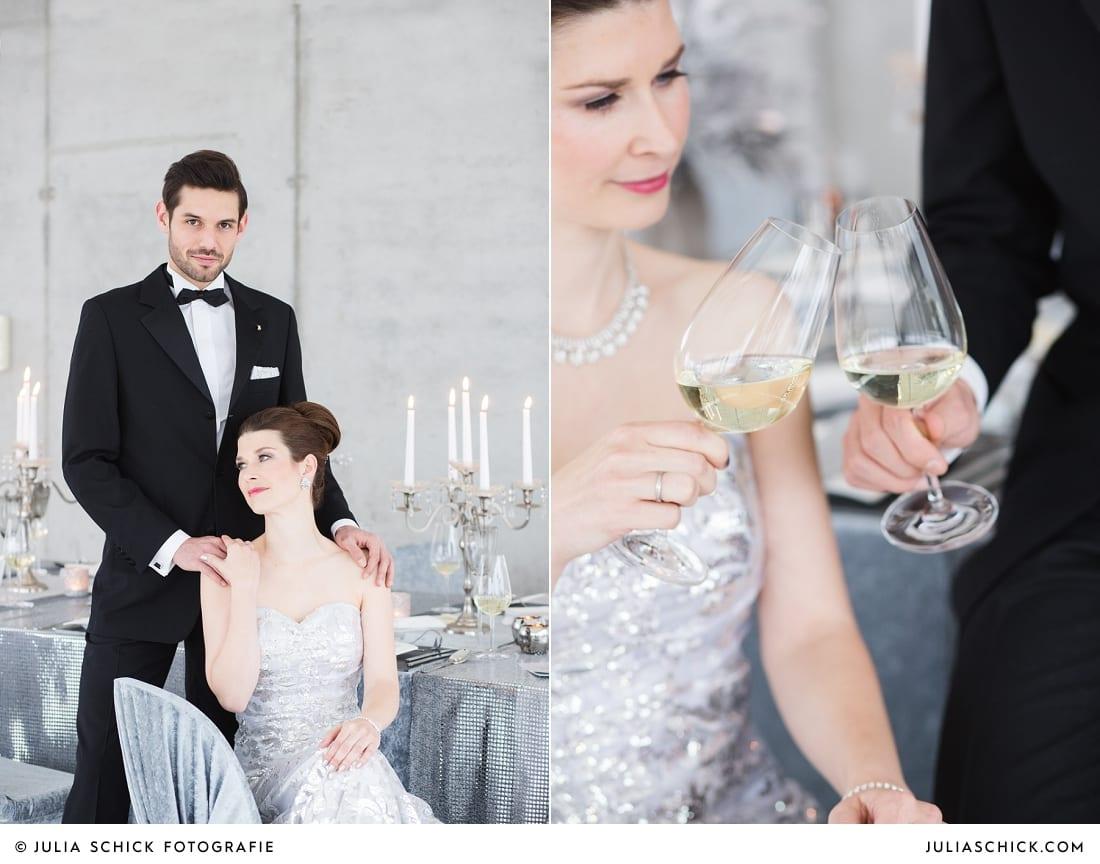 Brautpaar in Hochzeitsoutfits von MM Couture stößt mit Wein an und Tischdekoration passend zum Hochzeitskonzept zum Thema Beton meets Glamour im Fleet 3 in Hamburg Finkenwerder