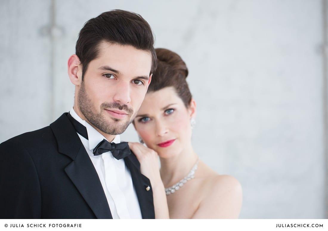 Braut in Brautkleid von MM Couture und Bräutigam in Smoking von MM Couture vor Betonwand in der Hochzeitslocation Fleet3 in Hamburg Finkenwerder
