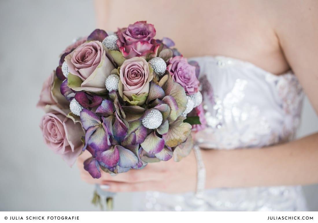 Braut in Brautkleid von MM Couture und und Brautstrauß in lila und silber vor Betonwand in der Hochzeitslocation Fleet3 in Hamburg Finkenwerder