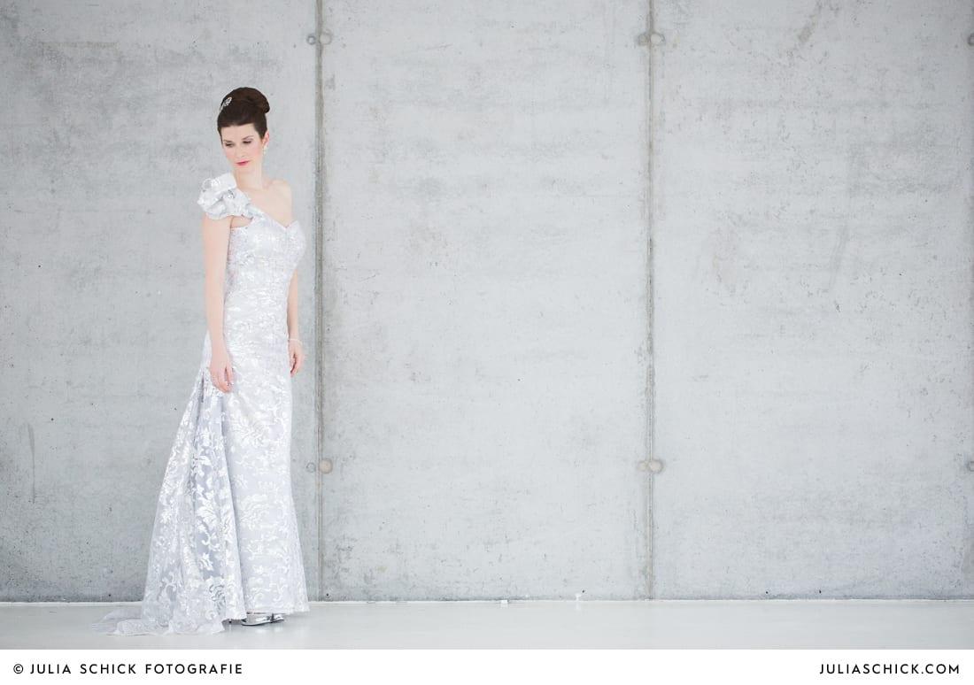 Braut in Brautkleid von MM Couture vor Betonwand in der Hochzeitslocation Fleet3 in Hamburg Finkenwerder
