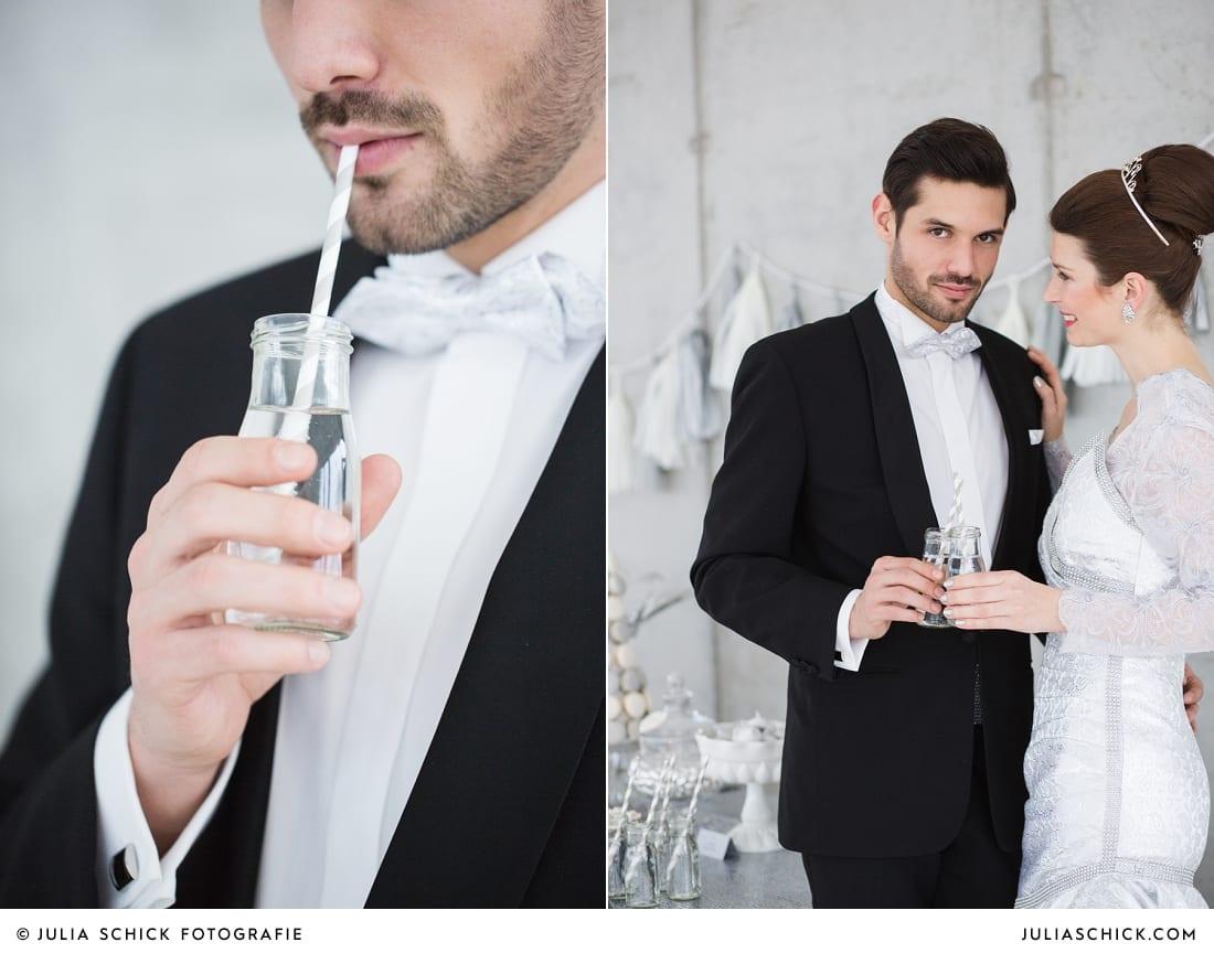 Bräutigam mit Fliege und Smoking von MM Couture und Braut in Kleid von MM Couture trinken Champagner aus Mason bell Glas
