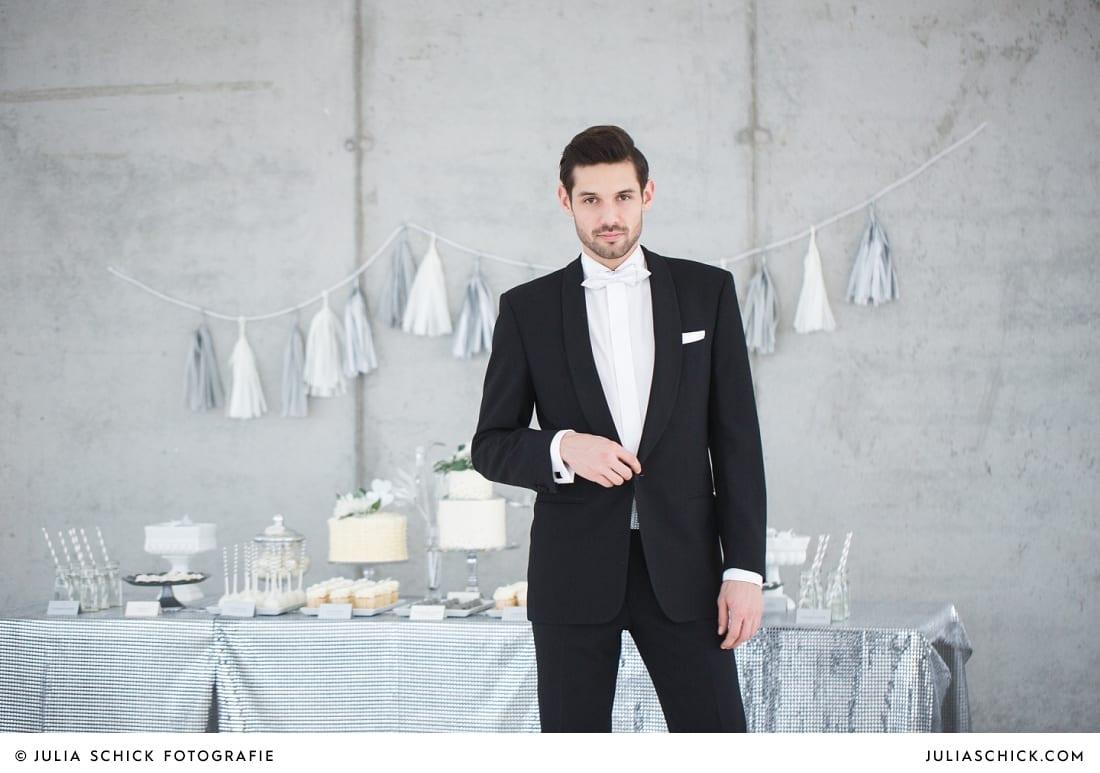 Bräutigam in Smoking von MM Couturevor Candybar und Sweettable von Zuckermonarchie vor Betonwand in der Hochzeitslocation Fleet3 in Hamburg Finkenwerder