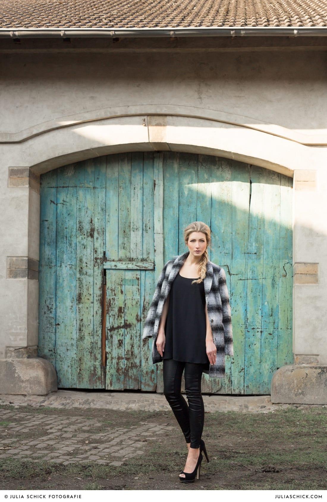 Fashionshooting von Modefotografin Julia Schick und Make-up-Artist Sandra Globke. Frau in schwarzem Outfit mit gestreiftem Mantel von H&M vor türkisem Tor in Bochum.