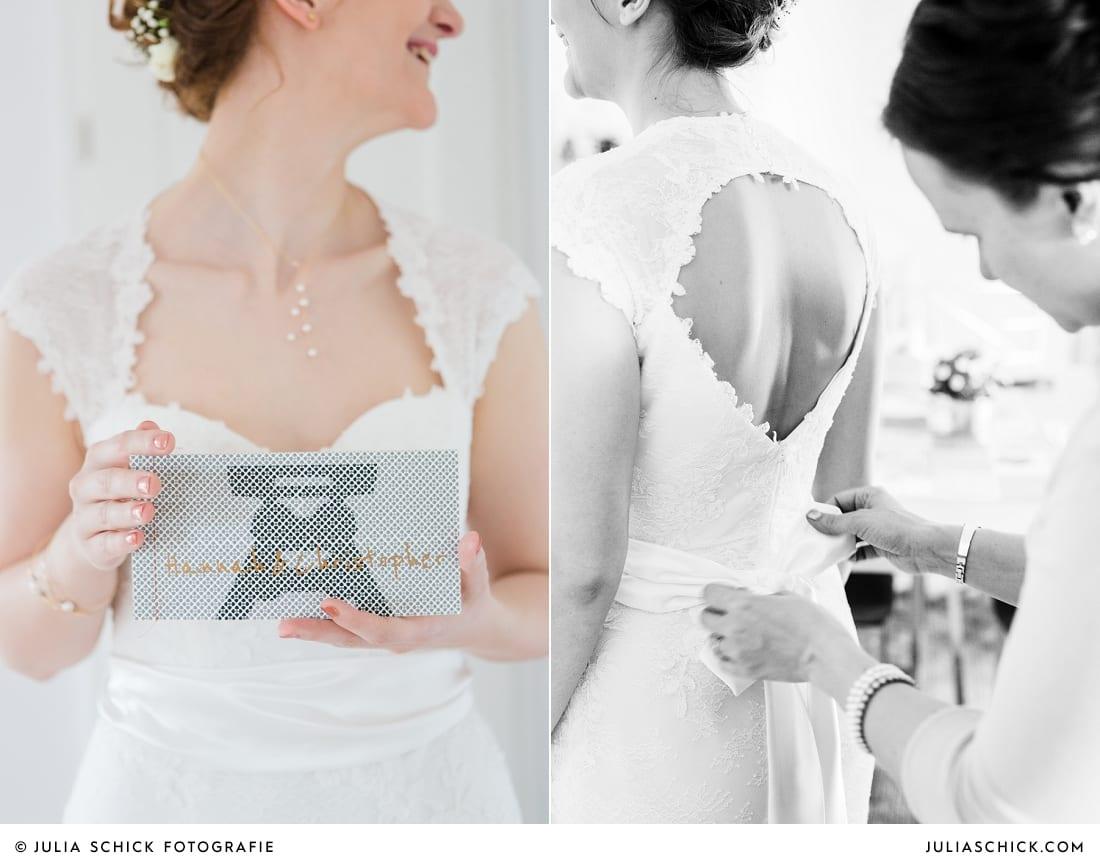 Trauzeugin bindet Schleife am Kleid der Braut, Braut hält Hochzeitseinladung mit Ruhrpott-Thema in der Hand