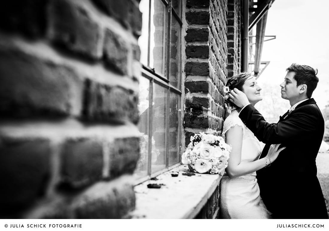 Brautpaar lehnt an Backsteinwand bei Hochzeitsfotoshooting auf der Künstlerzeche Unser Fritz in Herne