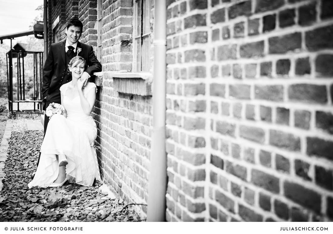 Brautpaar sitzt an Backsteinwand bei Hochzeitsfotoshooting auf der Künstlerzeche Unser Fritz in Herne