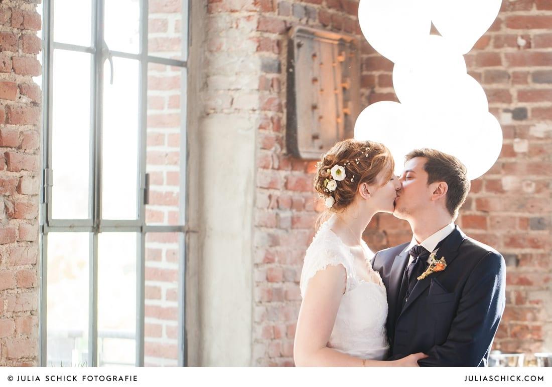 Küssendes Brautpaar mit Luftballons bei Hochzeitsfeier auf der Künstlerzeche Unser Fritz in Herne