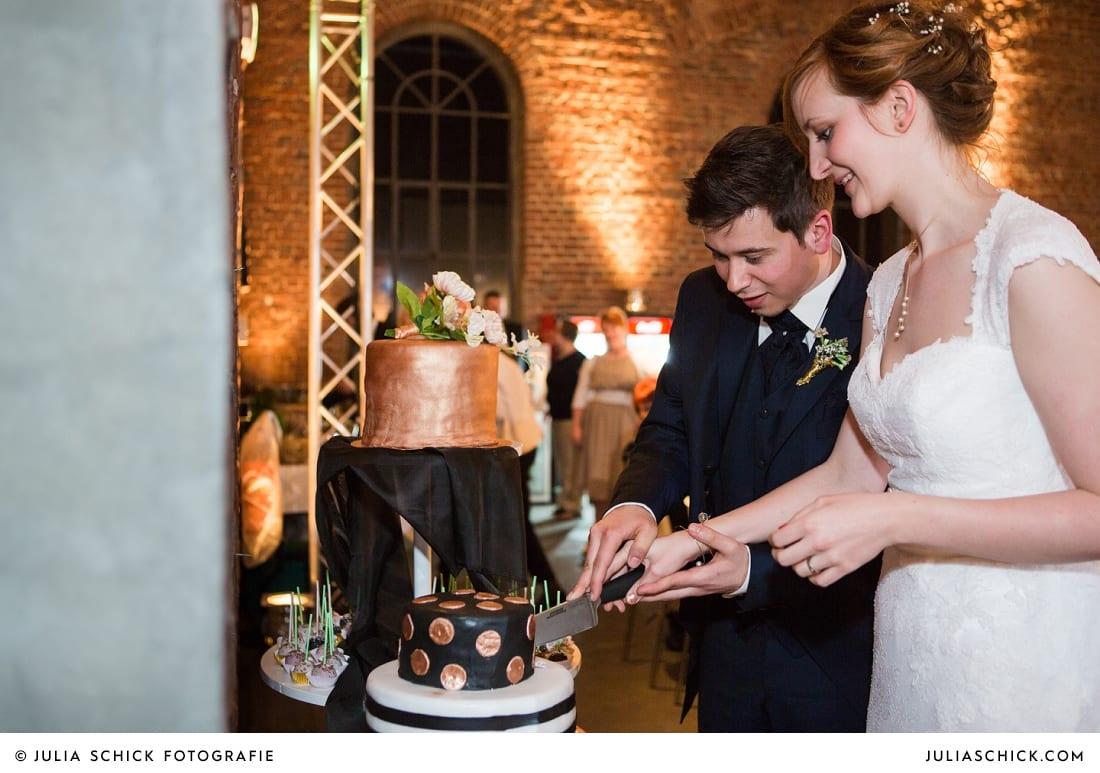 Brautpaar schneidet Hochzeitstorte an bei Hochzeitsfeier auf der Künstlerzeche unser Fritz