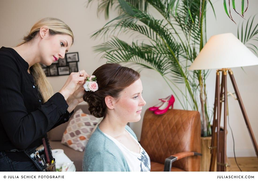 Visagistin Sandra Globke stylt eine Brautfrisur mit rosen im Haar