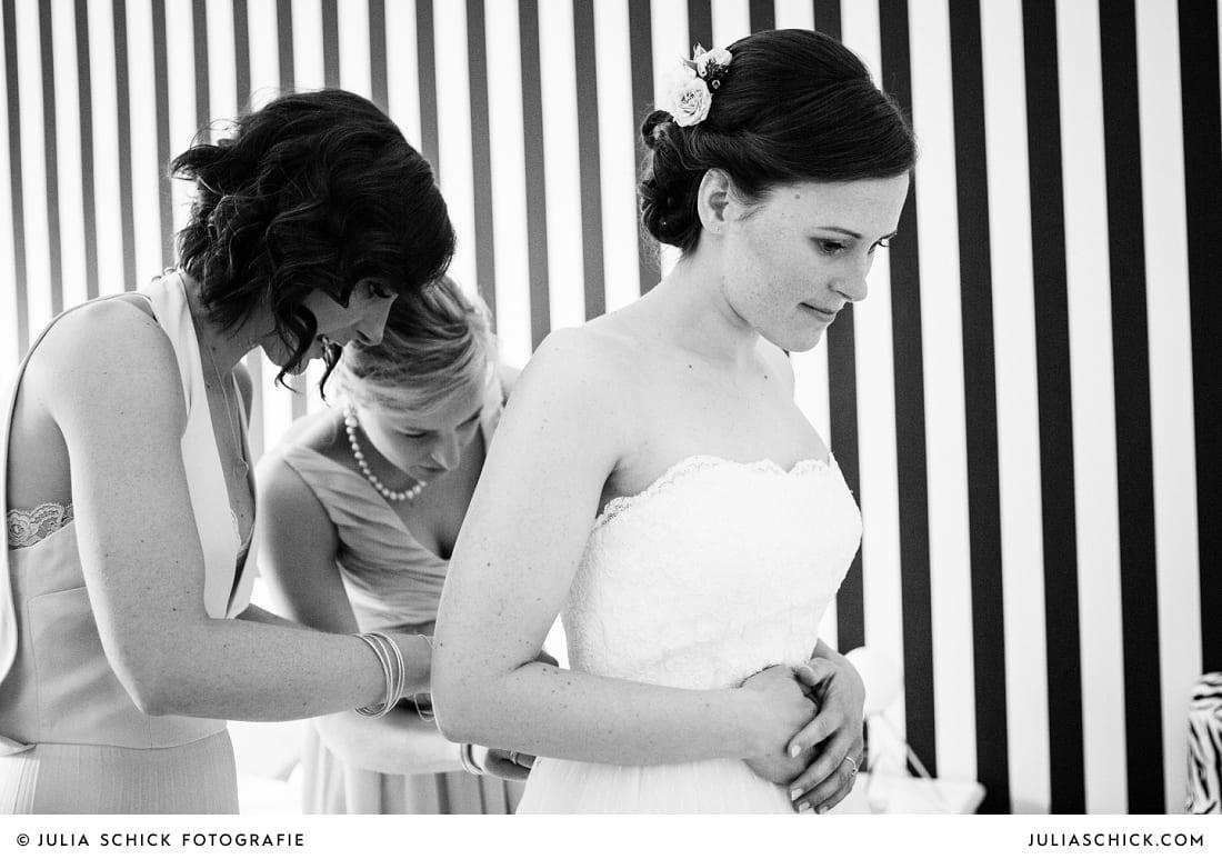 Trauzeuginnen helfen Braut beim Ankleiden