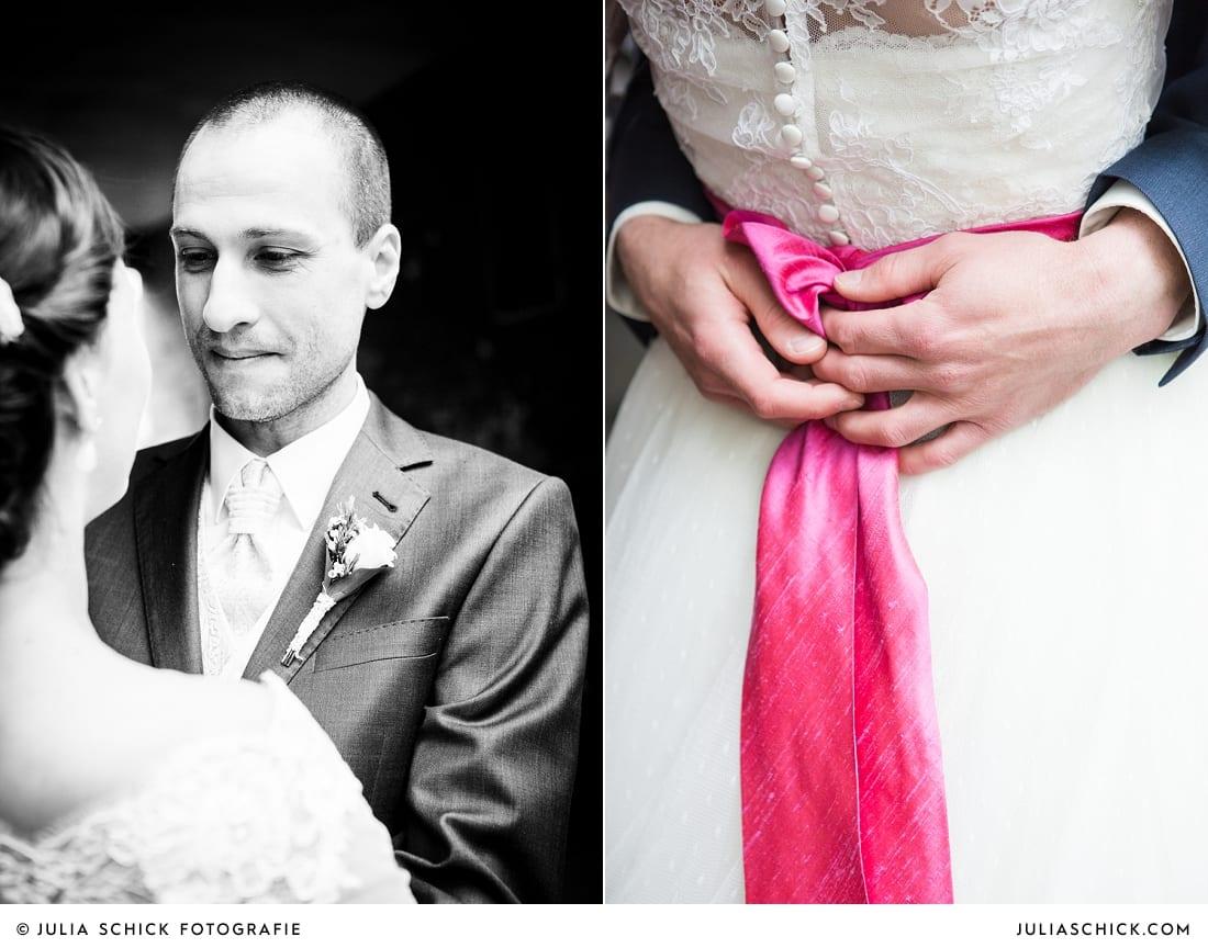 Verliebter Blick des Bräutigams auf seine Braut, Brautkleid mit pinkem Gürtel