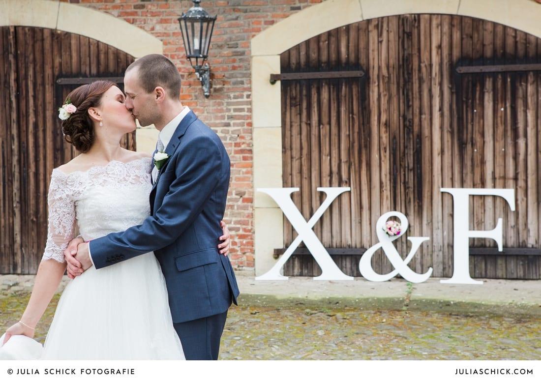 Brautpaar auf Burg Hülshoff mit großen Holzbuchstaben
