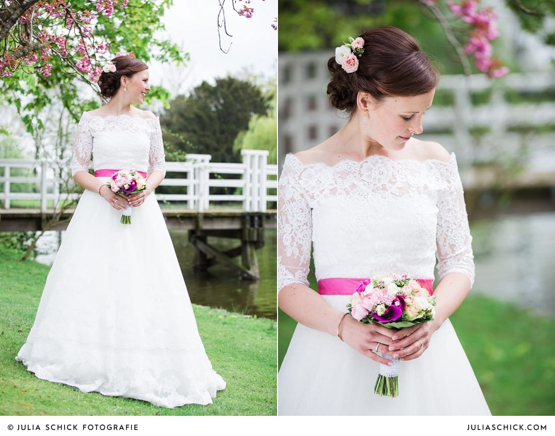 Braut in Brautkleid von Pronovias mit pinkem Gürtel auf Burg Hülshoff miit Kirschblüten