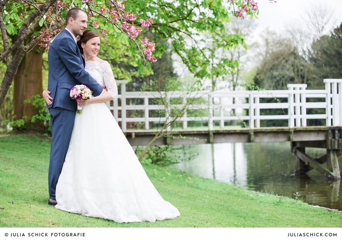 Bräutigam in blauem Anzug und Braut in Brautkleid von Pronovias mit pinkem Gürtel auf Burg Hülshoff mit Kirschblüten