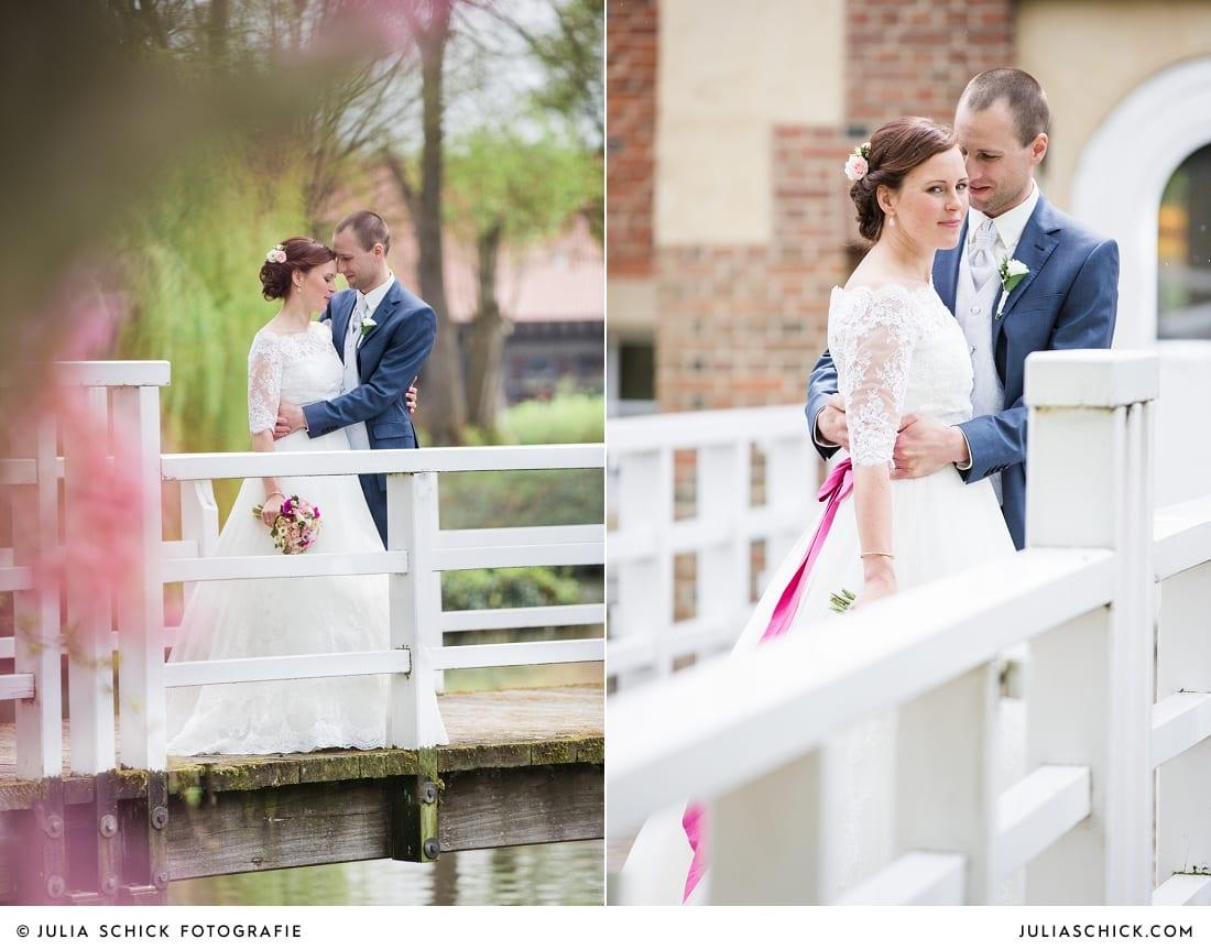 Bräutigam in blauem Anzug und Braut in Brautkleid von Pronovias mit pinkem Gürtel auf Burg Hülshoff miit Kirschblüten