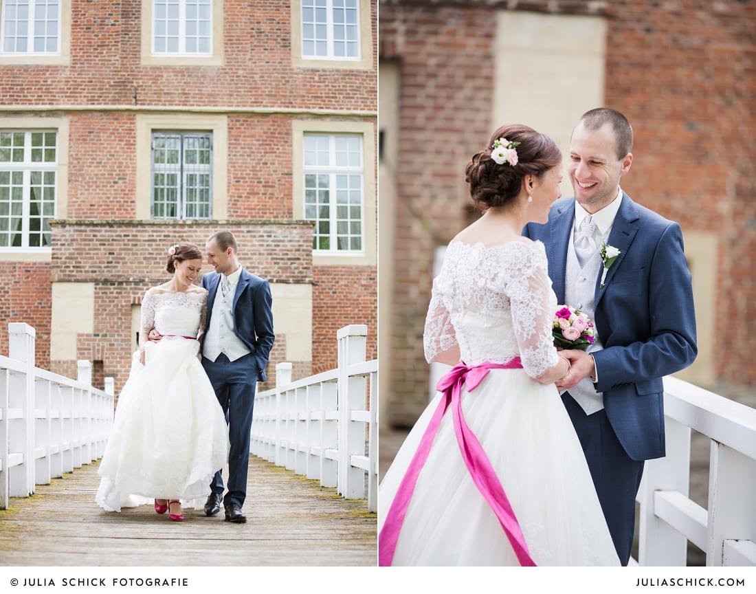 Bräutigam in blauem Anzug und Braut in Brautkleid von Pronovias mit pinkem Gürtel auf Brücke vor Burg Hülshoff