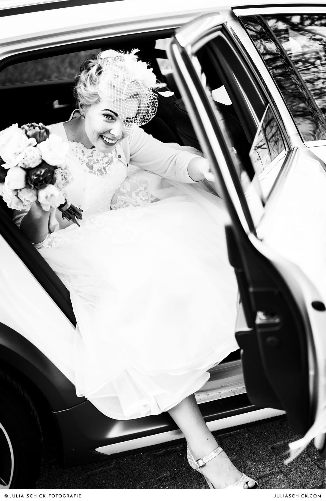 Braut in kurzem Kleid von Justin Alexander steig aus dem Auto