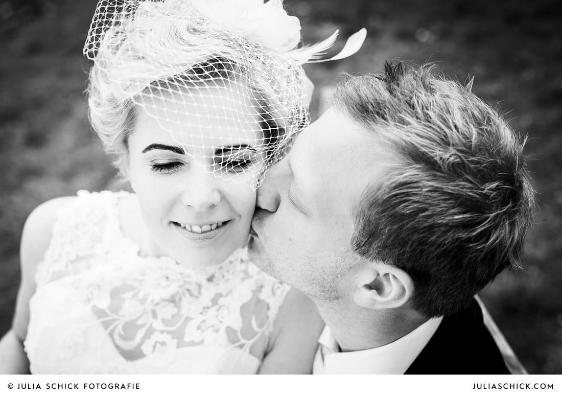 Bräutigam küsst Braut mit Fascinator beim Hochzeitsfotoshooting auf die Wange