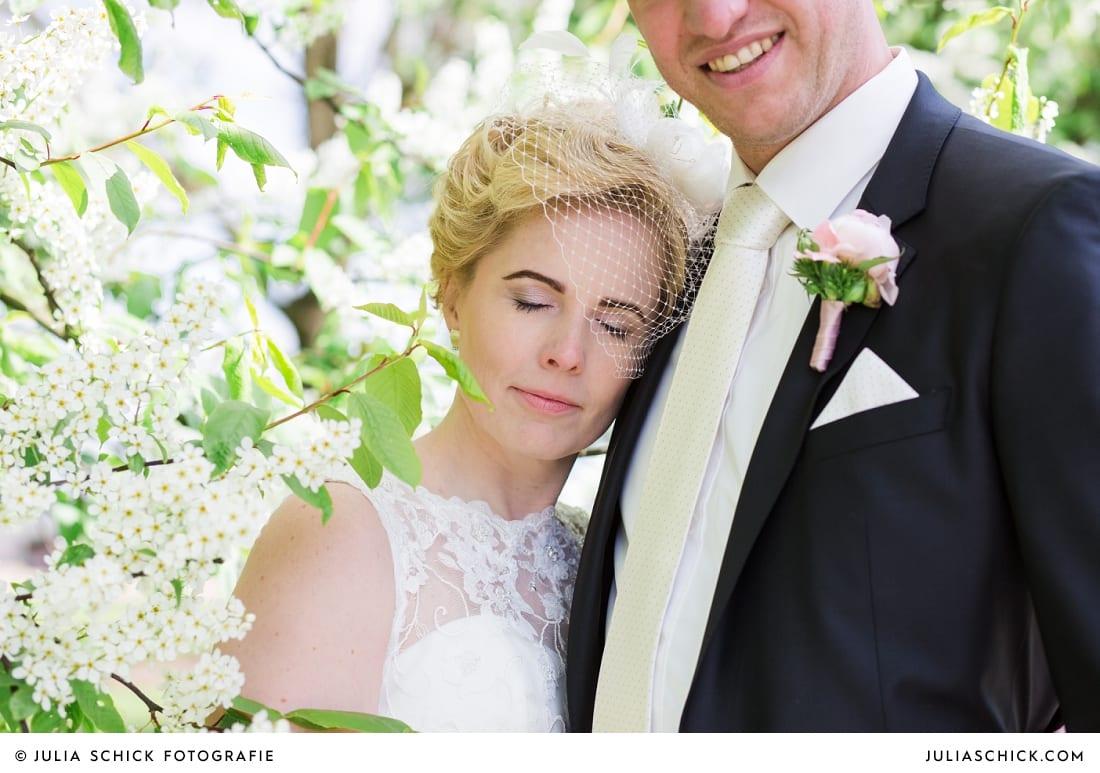 Brautpaar vor blühendem Baum bei Brautpaarshooting in den Baumbergen in Havixbeck