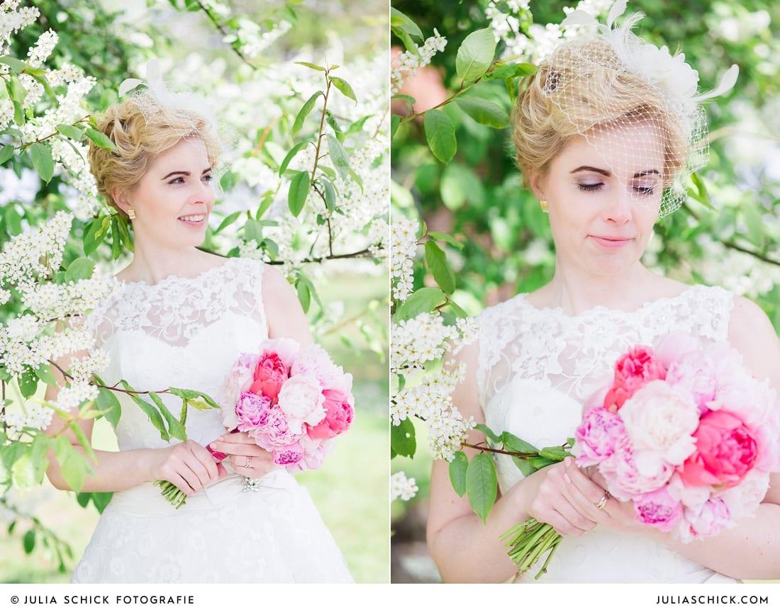 Braut mit Brautstrauß mit Pfingstrosen vor blühendem Baum bei Brautpaarshooting in den Baumbergen in Havixbeck