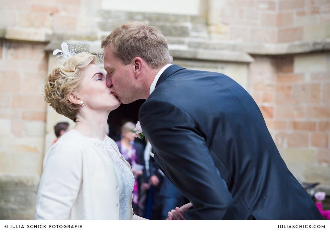 Küssendes Brautpaar vor der Kirche St. Dionysius in Havixbeck