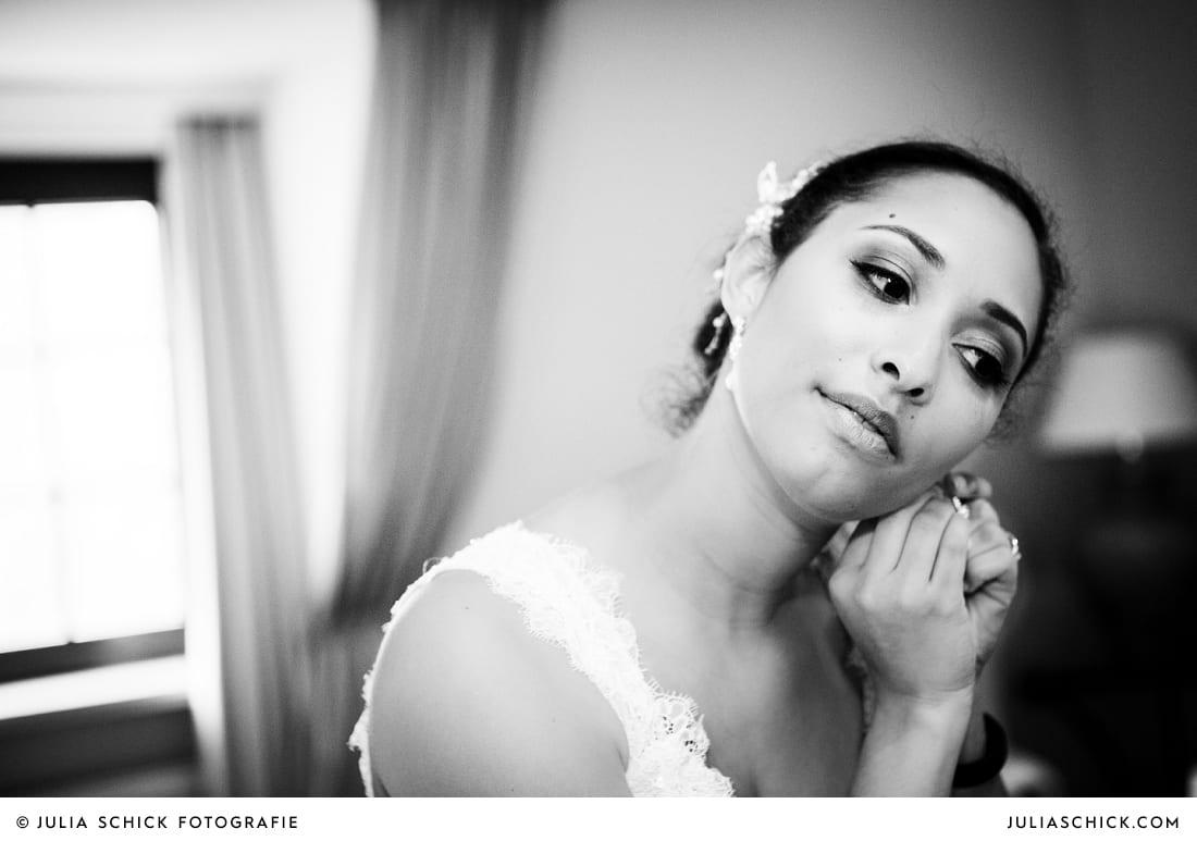Braut legt Ohrringe an vor standesamtlicher Trauung auf Sportschloss Velen im weißen Saal der Orangerie