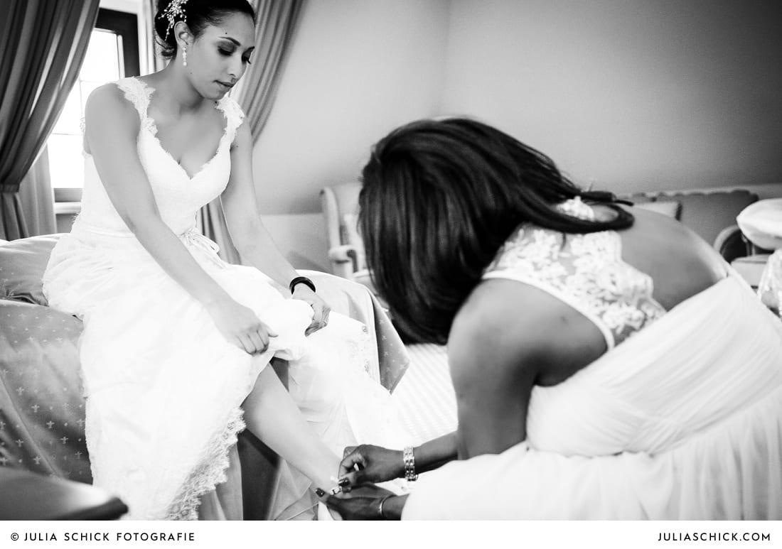 Brautmutter zieht Braut die Schuhe an auf Hotelzimmer standesamtlicher Trauung auf Sportschloss Velen im weißen Saal der Orangerie