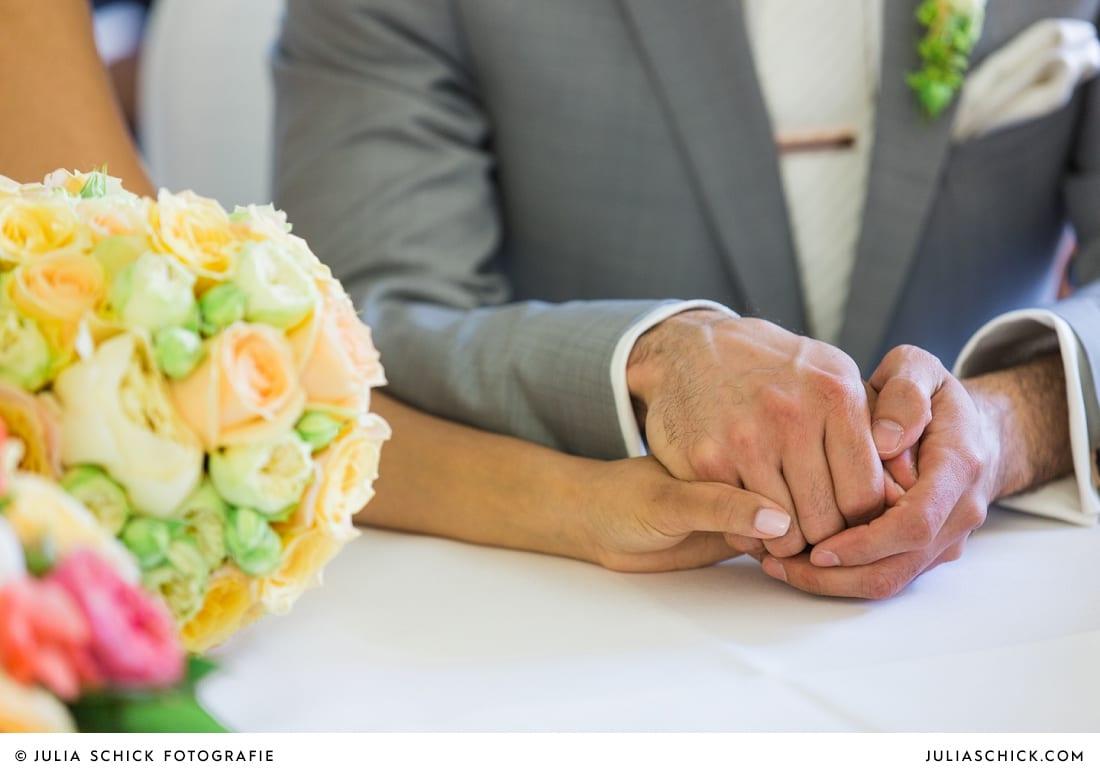 Hände des Brautpaares bei standesamtlicher Trauung auf Sportschloss Velen im weißen Saal der Orangerie