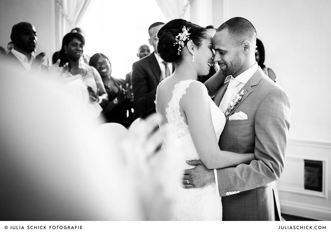 Küssendes Brautpaar bei standesamtlicher Trauung auf Sportschloss Velen im weißen Saal der Orangerie