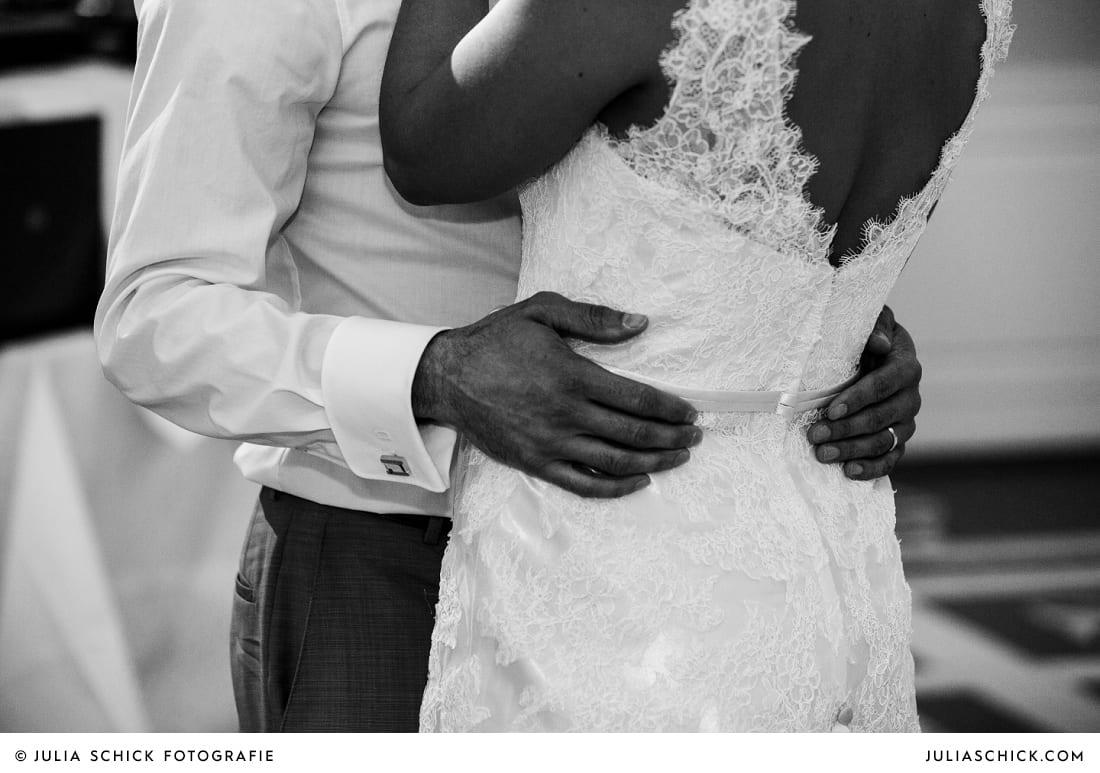 Hände des Bräutigams auf Kleid der Braut bei Hochzeitsfeier in der Remise des SportSchloss Velen