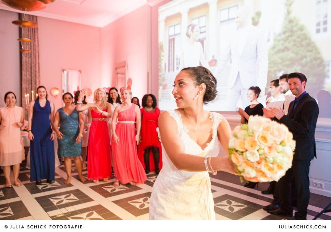 Braut wirft Brautstrauß bei Hochzeitsfeier in der Remise des SportSchloss Velen