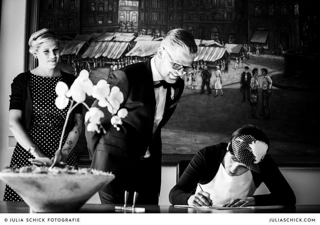Braut unterschreibt Eheurkunde bei standesamtlicher Trauung im alten Rathaus in Dortmund